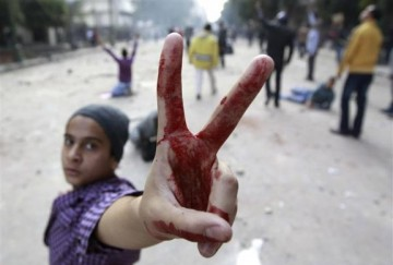 A protester flashes a victory sign as protesters throw stones at army soldiers at the cabinet near Tahrir Square in Cairo